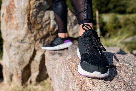 woman in jogging sneakers standing on rock