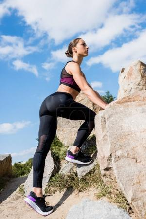 Photo for Athletic woman in modern sportswear climbing on rocks - Royalty Free Image