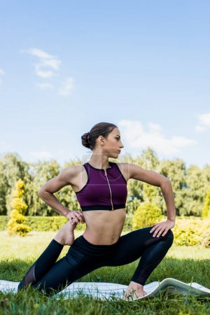 Photo for Beautiful woman in penguin pose practicing yoga outdoors - Royalty Free Image