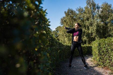 Photo pour Jeune femme qui s'étend dans le parc avant l'entraînement - image libre de droit
