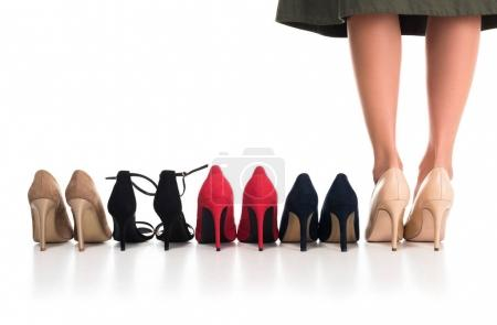 Photo for Cropped shot of female legs and arranged various fashionable high heels isolated on white - Royalty Free Image