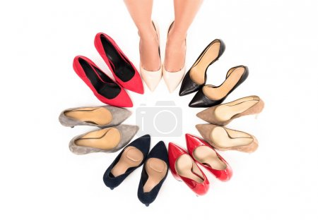 Photo for Partial view of woman standing in circle with arranged stylish high heels isolated on white - Royalty Free Image