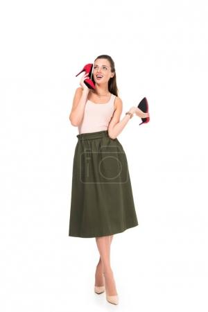 woman holding pair of red shoes
