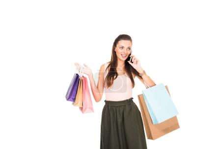 woman with shopping bags talking on smartphone