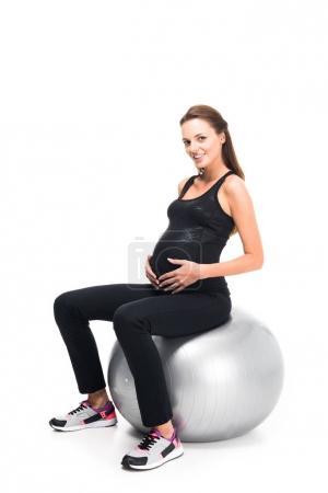 Photo pour Femme enceinte souriante faisant de l'exercice sur balle de fitness isolée sur blanc - image libre de droit
