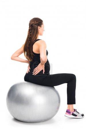 Photo pour Vue arrière de la femme enceinte faisant de l'exercice sur balle de fitness isolée sur blanc - image libre de droit