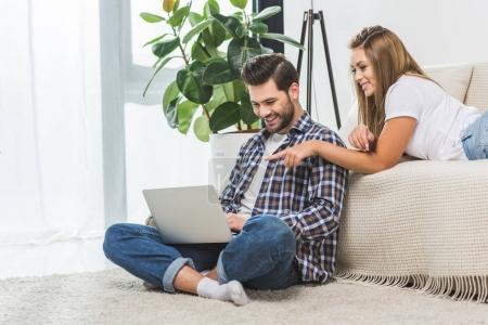 attractive couple using laptop