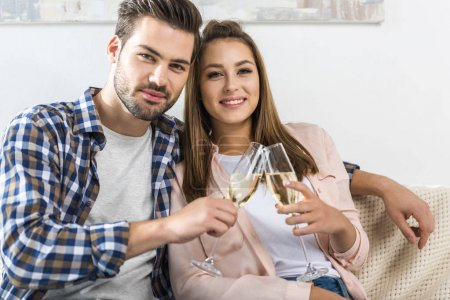 Photo for Young attractive couple embracing and clinking glasses of champagne, while looking at camera - Royalty Free Image