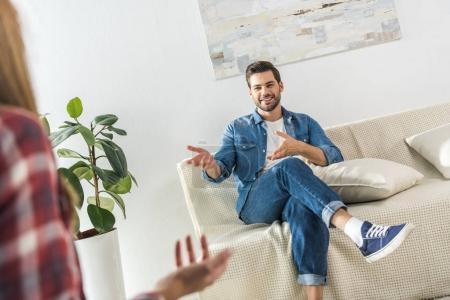Man on sofa talking to girlfriend