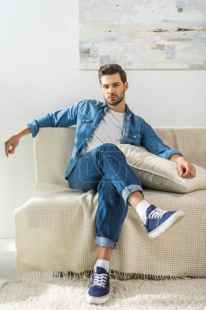 Photo for Young attractive man sitting on sofa at home with legs crossed and looking at camera - Royalty Free Image