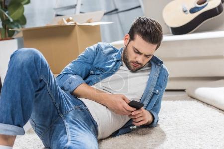 Photo pour Jeune homme séduisant, couché sur le plancher dans le salon tout en utilisant le smartphone - image libre de droit