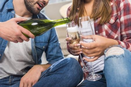 couple sitting on floor with champagne