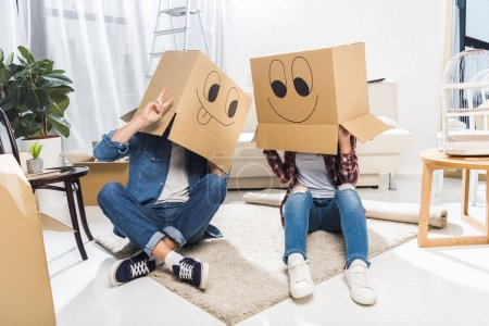 Photo for Young couple sitting on floor with boxes on their heads, that have smiley faces on them - Royalty Free Image