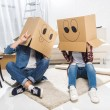 Young couple sitting on floor with boxes on their ...