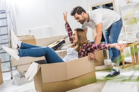 Young couple playing with moving boxes