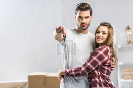 Photo for Young attractive couple hugging in living room with cardboard boxes and showing a key - Royalty Free Image