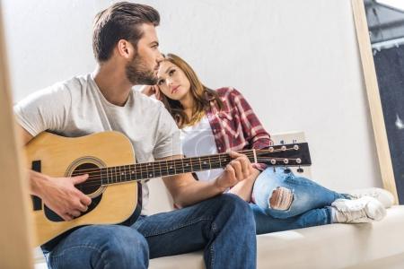 Photo pour Jeune couple assis sur le canapé dans le salon et jouer de la guitare - image libre de droit