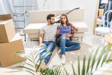Photo pour Jeune couple attrayant assis sur le sol dans le salon et montrant notre première maison signe - image libre de droit