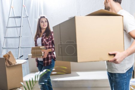 Photo for Young man holding a big cardboard box while his girlfriend is holding a stack of books - Royalty Free Image
