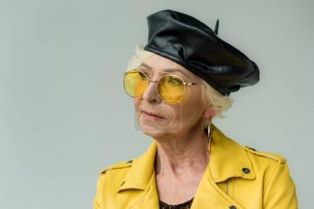 senior woman in beret and yellow sunglasses