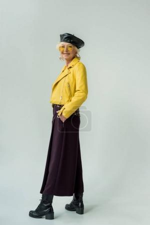Photo pour Fashionable senior woman in yellow leather jacket and yellow sunglasses, isolated on grey - image libre de droit