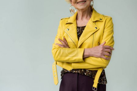 Photo for Cropped view of fashionable senior woman in yellow leather jacket and yellow sunglasses, isolated on grey - Royalty Free Image