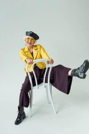 Photo pour La mode femme haute en cuir jaune veste et jaune lunettes de soleil assis sur la chaise, isolé sur fond gris - image libre de droit