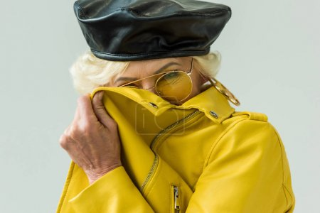 Photo for Stylish laughing senior woman in yellow leather jacket and yellow sunglasses, isolated on grey - Royalty Free Image