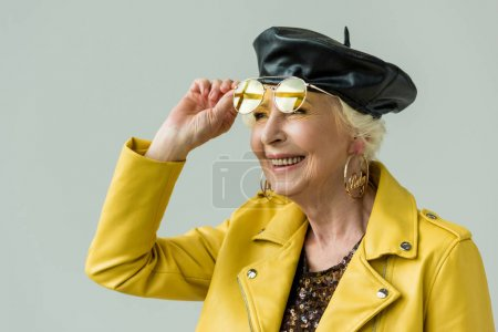 stylish senior woman in yellow sunglasses