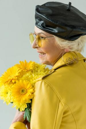 senior woman with bouquet of yellow flowers