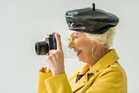 Photo for Stylish senior woman in yellow jacket and leather beret taking photo on camera, isolated on grey - Royalty Free Image