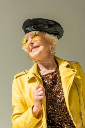 Foto de Elegante dama senior en amarillo chaqueta y boina de cuero, aislado en gris - Imagen libre de derechos