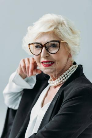 Photo pour Attractive senior lady with pearl necklace, isolated on grey - image libre de droit