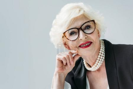 Photo pour Attractive senior lady with pearl necklace and eyeglasses, isolated on grey - image libre de droit