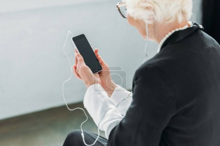senior lady listening music with smartphone
