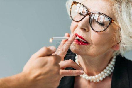 senior woman smoking cigarette