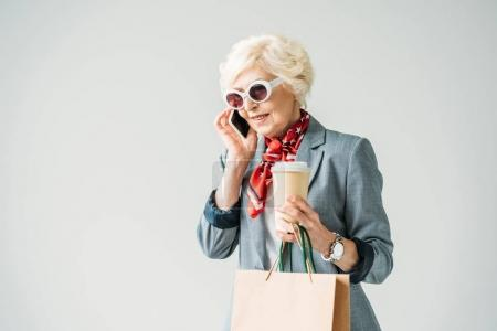 senior woman with shopping bags and smartphone
