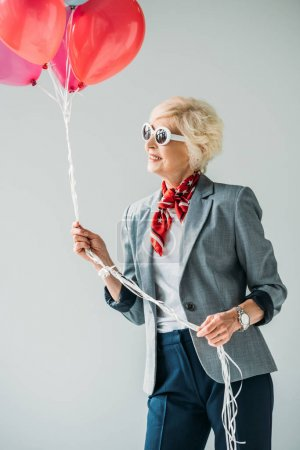 Photo for Stylish senior lady in jacket and sunglasses with balloons,  isolated on grey - Royalty Free Image