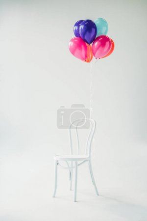 Colorful balloons tied to chair