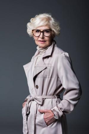 Photo pour Jolie femme senior en Trench-Coat, isolé sur fond gris - image libre de droit
