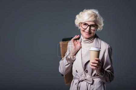 Seniorin mit Einkaufstaschen und Kaffee