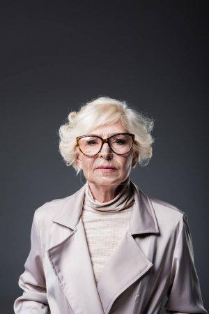 Photo pour Portrait de la belle dame senior en trench-coat et lunettes, isolés sur fond gris - image libre de droit