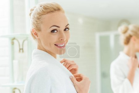 Photo for Beautiful young woman in bathrobe smiling at camera - Royalty Free Image