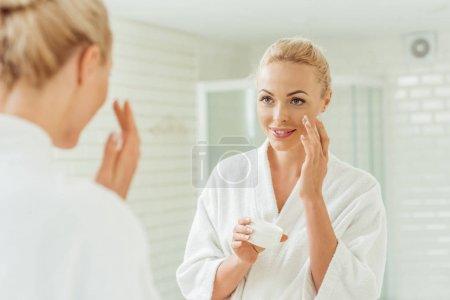 Photo pour Belle jeune femme souriante en peignoir appliquant crème visage - image libre de droit