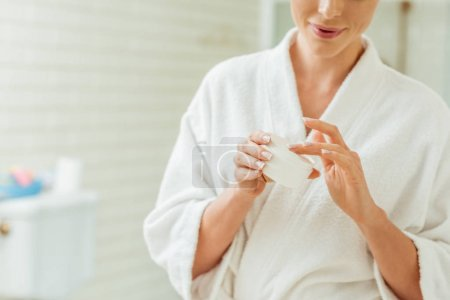woman in bathrobe applying face cream