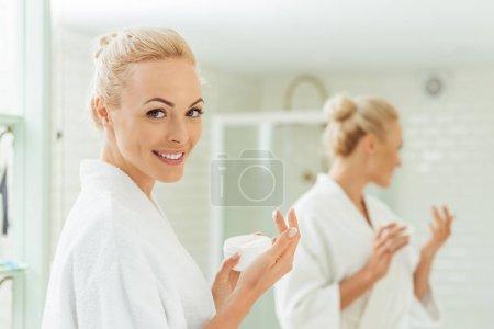 woman in bathrobe applying face cream