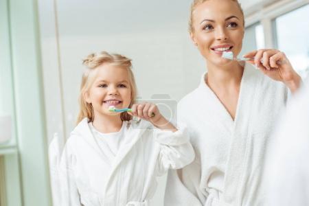 Photo pour Adorable sourire mère et fille en peignoirs brossant les dents ensemble - image libre de droit