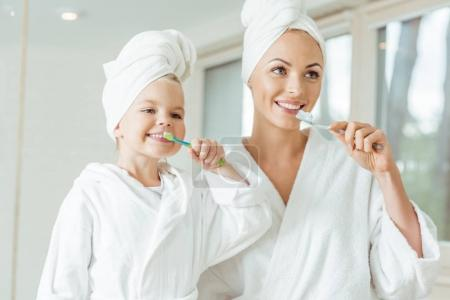 Photo for Happy mother and daughter in bathrobes and towels brushing teeth together - Royalty Free Image