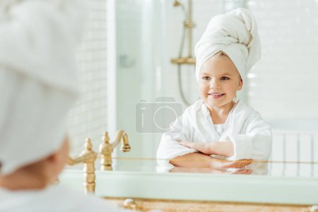 Photo pour Belle petite fille heureuse en peignoir et serviette sur la tête en regardant miroir dans la salle de bain - image libre de droit