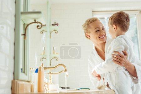Photo pour Belle mère heureuse en fils portant des peignoirs et se souriant dans la salle de bain - image libre de droit